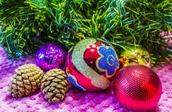Christmas, New Year background. Behind the artificial Christmas tree, red glass balls and cones, decorations on a pink background Stock Image