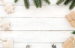 Christmas and New Year background. Christmas present gift boxes, fir leaves, pine cones with decoration rustic elements on white wood background. Creative flat Stock Photography