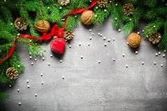 Christmas and New Year background. Christmas tree branch on a black background. Cones and fur-tree toys. View from above. Copy space stock image