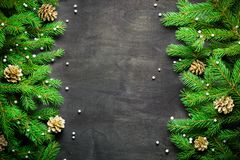 Christmas and New Year background. Christmas tree branch on a black background. Cones and fur-tree toys. View from above. Copy space royalty free stock image