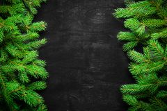 Christmas and New Year background. Christmas tree branch on a black background. Cones and fur-tree toys. View from above. Copy space royalty free stock photography