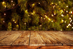 Christmas and New year background with empty dark wooden deck table over christmas tree and blurred light bokeh. Empty display for product montage. Rustic royalty free stock images