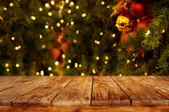 Christmas and New year background with empty dark wooden deck table over christmas tree and blurred light bokeh.
