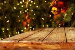 Christmas and New year background with empty dark wooden deck table over christmas tree and blurred light bokeh. Royalty Free Stock Photos