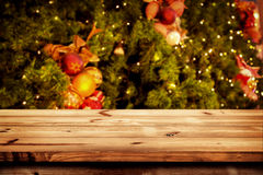 Christmas and New year background with empty dark wooden deck table over christmas tree and blurred light bokeh. Stock Photos