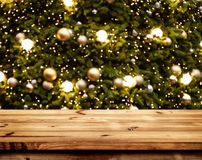 Christmas and New year background with empty wooden deck table. Over blurred christmas tree at night. Empty display for product montage. Rustic scene stock images