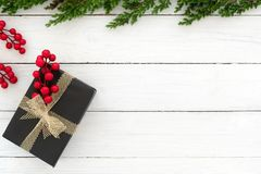 Christmas and New Year background. With fir branches, gift box and holly berry on white wooden background. Creative Flat layout and top view composition stock image