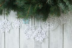 Christmas or New Year background with fir branches and knitted white snowflakes on a white background. royalty free stock photos