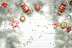 Christmas or New Year background: fur-tree branches, colorful glass balls, decoration and glittering stars on white wood Royalty Free Stock Images