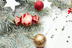 Christmas or New Year background: fur-tree branches, colorful glass balls, decoration and glittering stars on white wood Royalty Free Stock Image