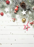 Christmas or New Year background: fur-tree branches, colorful glass balls, decoration and glittering stars on white wood Stock Image