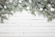 Christmas or New Year background: fur-tree branches, decoration and glittering stars on wooden background, top view Royalty Free Stock Photos