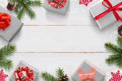 Christmas New Year background with gifts and free space for text. White wooden board with Christmas tree branches, pinecones, and snowflake decorations stock photography