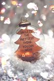 Christmas and new year background - glass ball with quote `a smile is the prettiest thing you can wear`, candle and christmas ligh Royalty Free Stock Photography