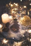 Christmas and new year background - glass ball with quote `a smile is the prettiest thing you can wear`, candle and christmas ligh Stock Images