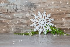 Christmas and new year background. Large white snowflake on a gray table with a green branches with reflection. On wooden background vintage Royalty Free Stock Photos