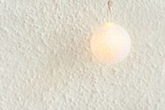 Christmas New Year Background. Pastel Golden Cotton Ball of Garland on White Wall Background. Scandinavian Style. Glowing Light stock photo