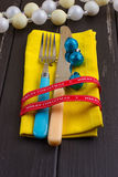 Christmas New Year background. set fork, knife, spoon on yellow napkin with decoration Holiday gold ribbon, blue ball Stock Image