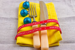 Christmas New Year background. set fork, knife, spoon on yellow napkin with decoration Holiday gold ribbon, blue ball Stock Photos