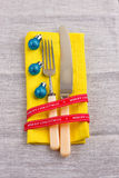 Christmas New Year background. set fork, knife, spoon on yellow napkin with decoration Holiday gold ribbon, blue ball Royalty Free Stock Images