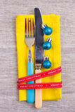 Christmas New Year background. set fork, knife, spoon on yellow napkin with decoration Holiday gold ribbon, blue ball Stock Photography