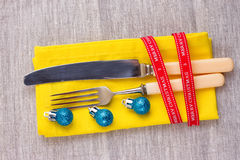 Christmas New Year background. set fork, knife, spoon on yellow napkin with decoration Holiday gold ribbon, blue ball Royalty Free Stock Photography