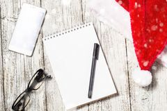 Christmas and New Year background with smartphone, red Santa hat, glasses, notepad and pen for your wishes. Decorated with snow royalty free stock photo