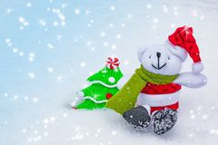 Christmas and new year background. Toy Christmas tree and white dog in a red Christmas hat with ornaments. On natural snow Stock Images