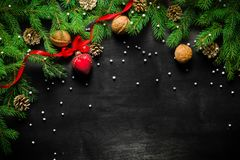 Christmas and New Year background. Christmas tree branch on a black background. Cones and fur-tree toys. View from above. Copy space stock images