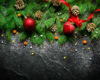 Christmas and New Year background. Christmas tree branch on a black background. Cones and fur-tree toys. View from above. Copy space stock photos