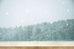 Christmas and New year background. Wooden table with winter snow. Fall covered forest. Vintage color tone and rustic style. Can be used product display royalty free stock photos