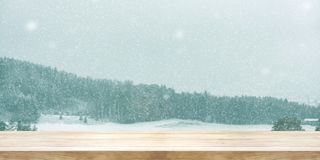 Christmas and New year background. Wooden table with winter snow. Fall covered forest. Vintage color tone and rustic style. Panoramic banner. Can be used product stock photos