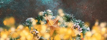 Christmas or New Year banner composition with green snow fir bra. Nches, pine cones, golden bokeh lights and Christmas star on brown background, top view stock photography