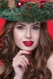 Christmas or New Year beauty girl portrait isolated on red background. Beautiful woman with luxury makeup and christmas wreath on. Head. Christmas mood Stock Photo