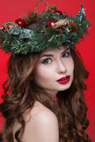 Christmas or New Year beauty girl portrait isolated on red background. Beautiful woman with luxury makeup and christmas wreath on. Head. Christmas mood Royalty Free Stock Images