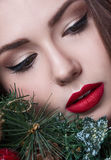Christmas or New Year beauty girl portrait isolated on red background. Beautiful woman with luxury makeup and christmas wreath on. Head. Christmas mood Stock Photos
