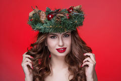Christmas or New Year beauty girl portrait isolated on red background. Beautiful woman with luxury makeup and christmas wreath on. Head. Christmas mood Royalty Free Stock Photography