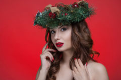 Christmas or New Year beauty girl portrait isolated on red background. Beautiful woman with luxury makeup and christmas wreath royalty free stock image