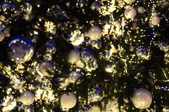 Christmas or New Year blurred bokeh background, christmas decorations silver and white balls on green pine branches close up stock image