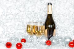 Christmas or New Year bottle of champagne, two full glasses of champagne on table, shiny and sparkling Christmas tree balls royalty free stock photos