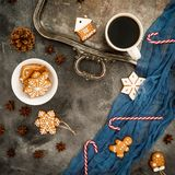 Christmas or New year breakfast. Frame of gingerbread, candy cane and coffee cup on dark table. Flat lay. Top view Stock Photos