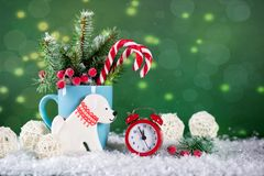 Christmas or new year card . On green bright background. Christmas or new year card . Cup with fir trees, candy canes and red clock and cookies in the shape of Stock Photo