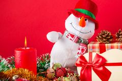 Christmas or New Year card. Funny snowman with burning candle, cones, giftbox anf spangle against red background. Stock Photos