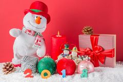 Christmas or New Year card. Funny snowman with burning candle, cones, giftbox, balls and 2018 figures on snow against red backgrou Royalty Free Stock Photography