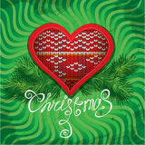Christmas and New Year card with knitted heart sha. Pe and fir tree branches on green background Stock Photo