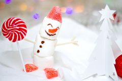 Christmas and new year card with snowman from marshmallow and red lollipop and a white Christmas tree made of paper, blurred royalty free stock images