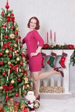 Christmas or New year celebration. Attractive young woman in red dress standing on one leg with another foot raised, near the Chri Stock Photography