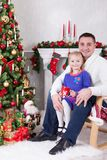 Christmas or New year celebration. Happy father and daughter sitting in chair near Christmas tree with xmas gifts. A fireplace wit Stock Photos