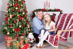 Christmas or New year celebration. Happy father and daughter sitting in chair near Christmas tree with xmas gifts. A fireplace wit Stock Image