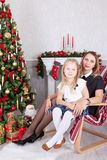 Christmas or New year celebration. Happy mother and daughter sitting in chair near Christmas tree with xmas gifts. A fireplace wit Royalty Free Stock Photos